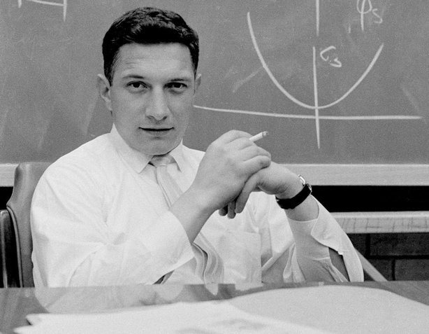 Robert Noyce seated at his desk in front of a diagram on a blackboard at Fairchild.