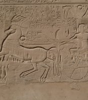 The north wall at the Temple of Karnak, where Seti I is shown mounting his chariot to make war with his enemies.