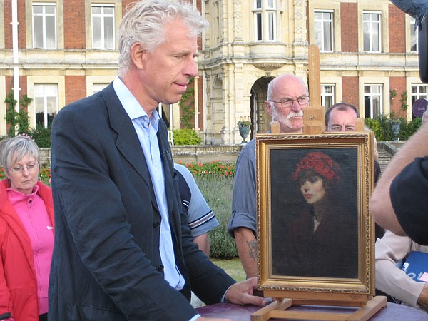 Paintings specialist Rupert Maas examines a portrait.