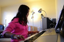 Nine-year-old Rachel Fang plays the piano in her home on the NMSU campus.