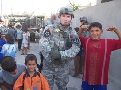 Retired Airborne Ranger Blake Hall poses with Kurdish kids during a combat to...