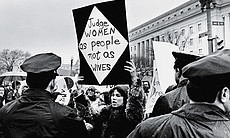 A young woman holds up a sign as she protests for women's rights in front of the Federal Trade Commission headquarters during Richard Nixon's inauguration weekend. Washington, D.C., January 18-21, 1969.