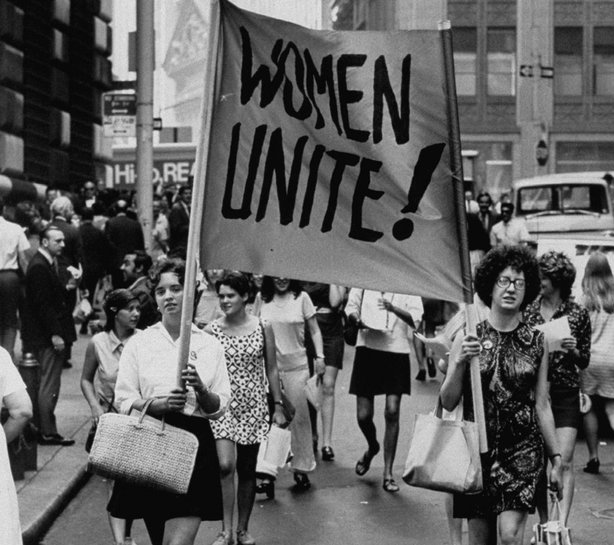 "Signs saying ""Women Unite"" carried by women supporters during a Women's Liberation demonstration on Fifth Avenue and on Wall Street, 1970."
