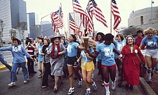 Leaders of the Women's Movement pass a torch that was carried by foot from New York to Houston, Texas, for the National Women's Convention. Among the marchers, front, from left to right: tennis star Billie Jean King, in blue shirt and tan pants; former U.S. Congresswoman Bella Abzug, wearing her trademark hat; and feminist writer Betty Friedan, right, in red coat. November 1977.