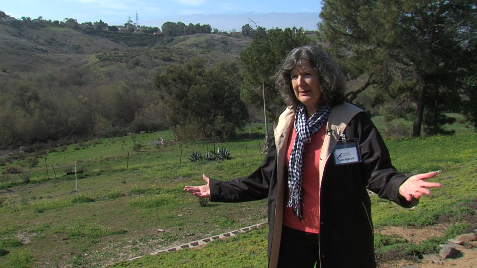 Diane Nygaard by the Marron Adobe, with land proposed for development behind