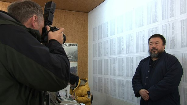 A foreign reporter photographs Ai Weiwei in front of the list of names of thousands of student earthquake victims, at his studio in Beijing.