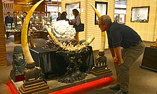 Bryan Christy examines an ivory sculpture, Beij...