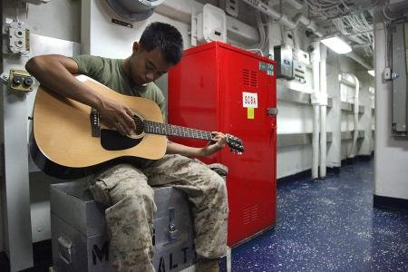 Corporal Bernard Vu, field radio operator, 2nd Platoon, Battery B, Battalion Landing Team 3/5, 15th Marine Expeditionary Unit, practices playing guitar aboard USS Rushmore, Feb. 27.