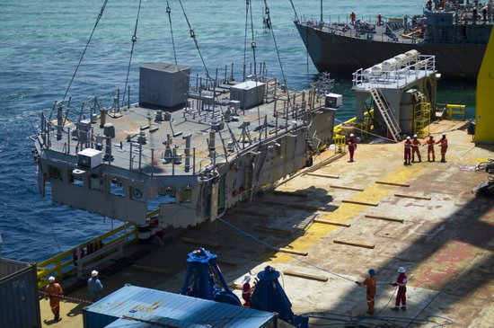 The second deck level of the mine countermeasures ship USS Guardian is guided onto the U.S. Navy contracted vessel M/V Jascon 25.