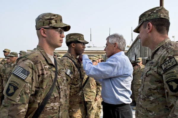 U.S. Defense Secretary Chuck Hagel presents a purple heart to a soldier in Ja...