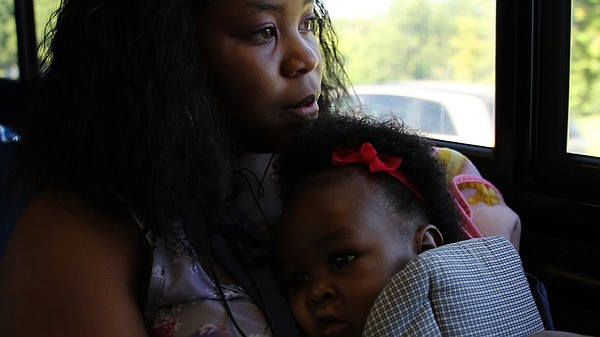 Raven Coston, a junior, makes her way to school on the bus with her young dau...