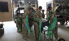 Military medics outside Camp Bastion hospital receive a battlefield casualty, Afghanistan.