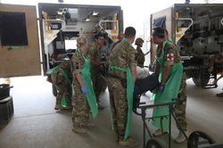 Military medics outside Camp Bastion hospital receive a battlefield casualty,...
