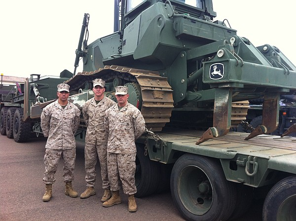 Three Marines in the 7th Engineer Support Brigade beside a D7 Bulldozer, one ...