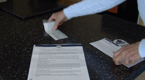Kathy Casey's refund check and a letter from the city of San Diego informing property owners they've been overcharged.
