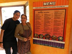 Rodnia and Rosario Sotelo pose in front of the menu at their restaurant, El B...