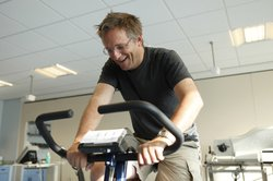 Dr. Michael Mosley on an exercise bike at University of Nottingham Medical School. He is performing his first ever session of High Intensity Training (HIT) on an exercise bike. Michael smiles as he is skeptical that cycling a total of three minutes a week can have just as many health benefits (if not more) than longer endurance training sessions.