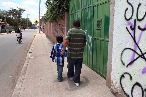 An American boy walks down a street in Guanajuato, Mexico with his father, a ...