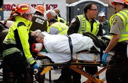 A man is loaded into an ambulance after he was injured by one of two bombs exploded during the 117th Boston Marathon near Copley Square on April 15, 2013 in Boston, Massachusetts.