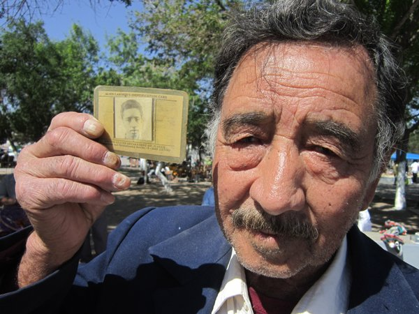 A former Bracero holds up his identification card from his days as a guest wo...