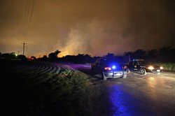 Smoke rises in the distance about half a mile from the West Fertilizer Compan...