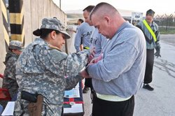 Capt. Karla Frey helps a soldier pin on his race bib at the 5K warrior run.