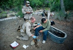 Border Patrol agents help an ailing migrant crosser.