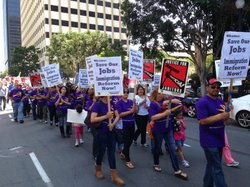 Hundreds of janitors marched through downtown San Diego on Friday to protest workplace immigration enforcement.