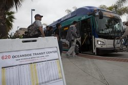 North County transit passengers catch a bus in Oceanside. Some of the passengers would rather take the Sprinter, but it's been shut down since March.