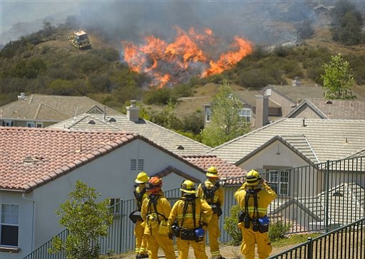 Firefighters from Glendale, Calif., and Pasadena, Calif., stand watch as bull...