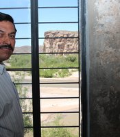 Bernardo Robles owns the casita in Boquillas, Mexico. Behind him, the Rio Grande and the United States. (Photo by Lorne Matalon)