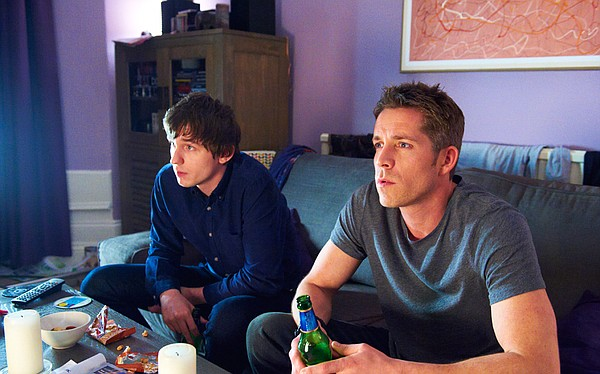 Dom and Sean watch television in Rachel's flat.