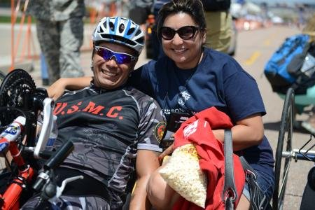 Marine Staff Sgt. Ronnie Jimenez celebrates his 10K hand-cycling win with his wife Patrice after crossing the finish line.