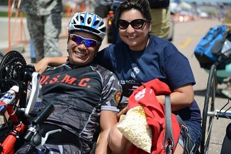 Marine Staff Sgt. Ronnie Jimenez celebrates his 10K hand-cycling win with his...