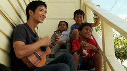 Jake Shimabukuro visits with children in his old neighborhood in Hawaii.