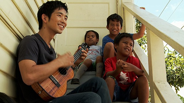 Jake Shimabukuro visits with children in his old neighbor...