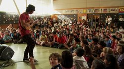 Jake Shimabukuro performs at an elementary school.