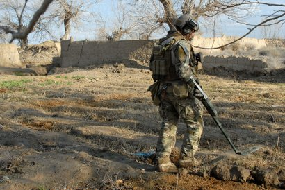 A U.S. Navy explosives ordnance disposal technician clears an area of explosives during operations March 2011, in Zharay District, Kandahar Province, Afghanistan.