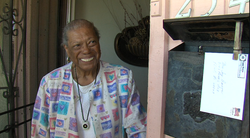 A District 4 voter opens her door to greet Myrtle Cole while she campaigns.