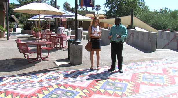KPBS reporter Claire Trageser and City Council District 4 candidate Dwayne Crenshaw stand on mosaic tiling in Market Creek Plaza.