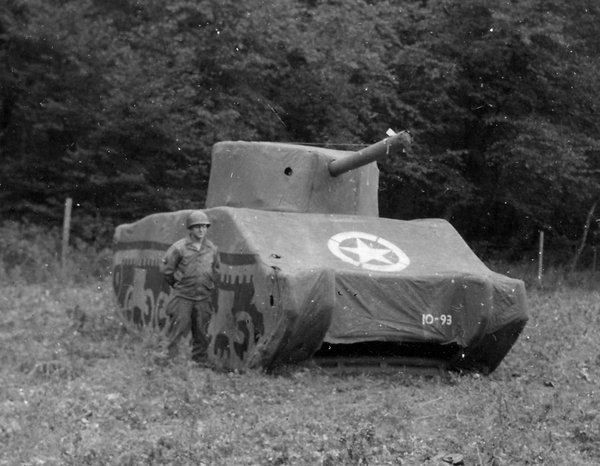 A Ghost Army soldier stands next to a rubber M4 Sherman t...