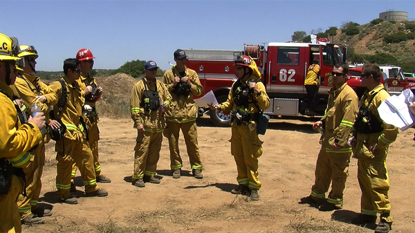 Firefighters meet up after completing a brush clearing tr...