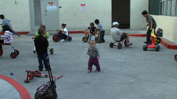 Shelter children ride bikes and play in the Rescue Mission's courtyard while ...