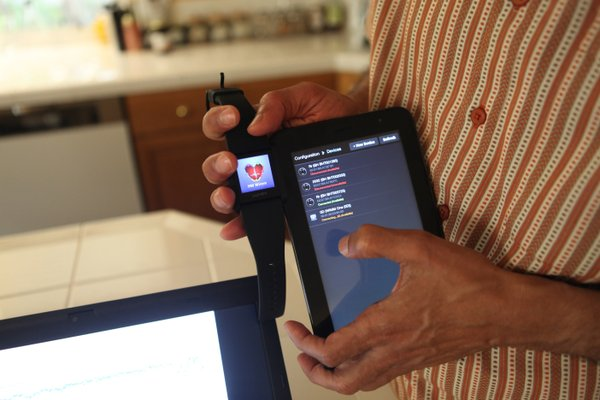 The wristwatch and tablet app used in the Bliss Buzzer sy...