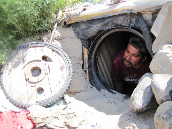 Jesus, a deportee, peeks out of the hole he dug into a ba...