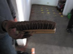 Juan Manuel Alvarez, deported last year, holds the brush he uses to shine sho...