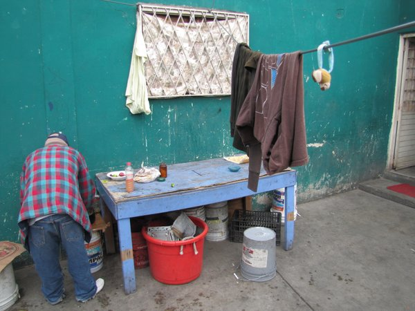 A man serves himself a plate of food at a Tijuana shelter...
