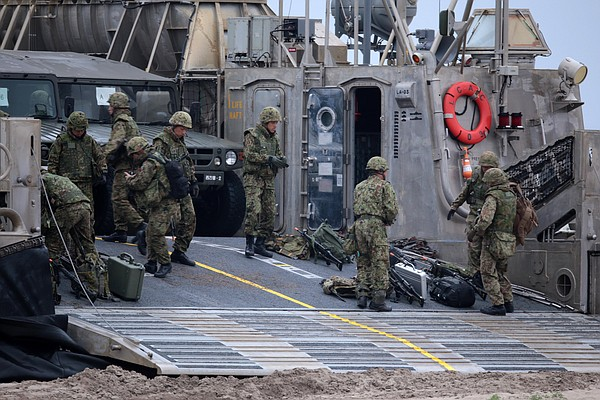 Japanese Ground Self Defense Force (JGSDF) soldiers unload weapons and vehicl...