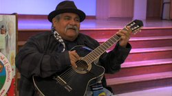 """Ramon """"Chunky"""" Sanchez plays his guitar inside the auditorium at King-Chavez Academy, which now bears his name."""
