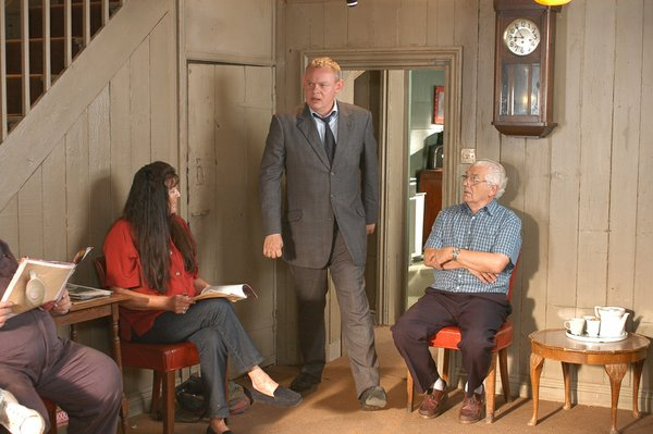 Martin Clunes as Doc Martin (center) in a waiting room filled with patients.